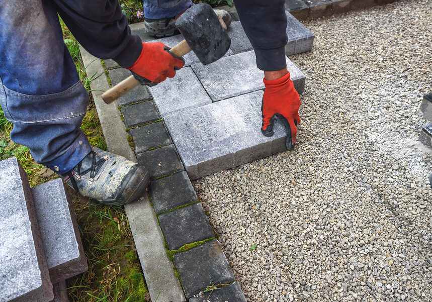 paving blocks. hand with rubber hammer install paving block
